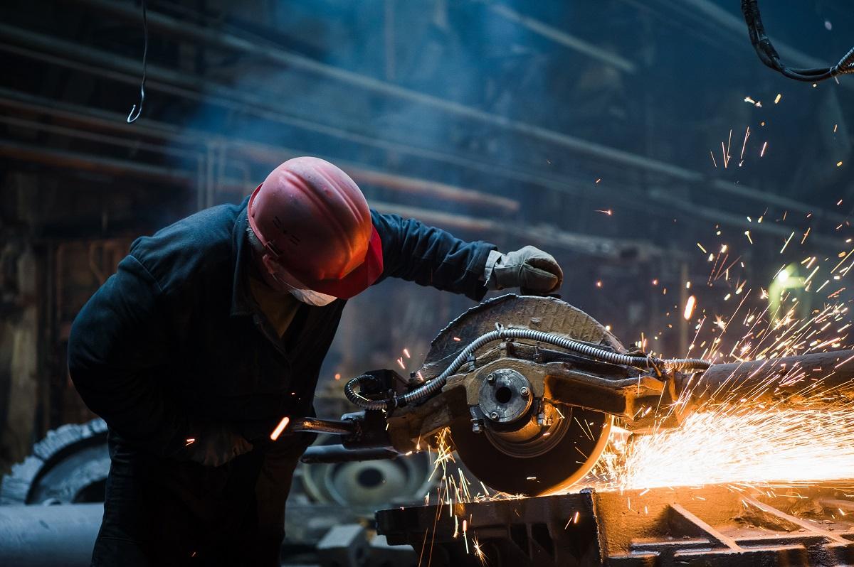 Employee grinding steel with sparks - focus on grinder. Steel factory.