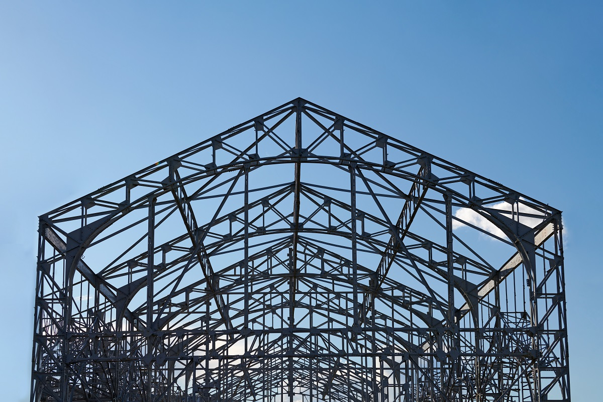 Frame of goods shed. Metal construction of railway building. Old abandoned steel warehouse for goods.