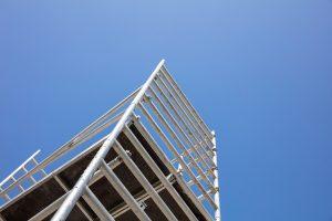 Scaffolding, metal mobile scaffold aginst blue sky background.