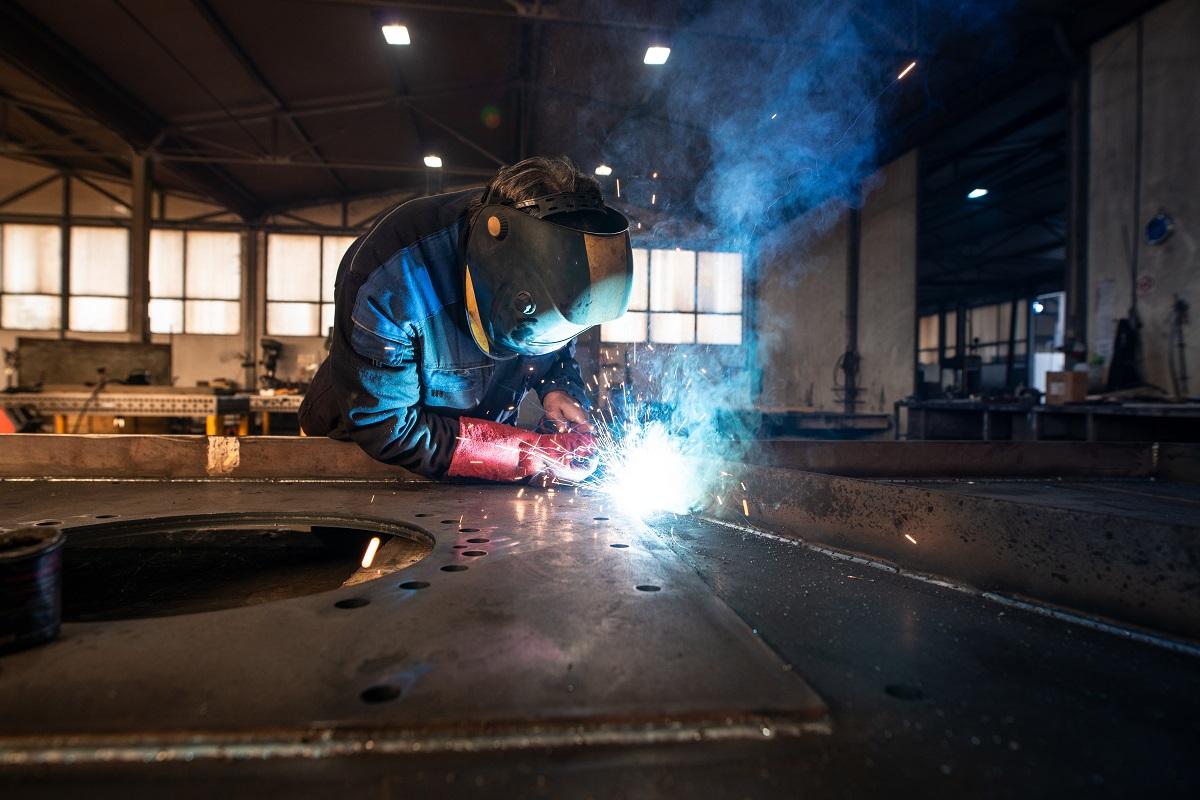 Professional industrial welder welding metal parts in metalworking factory.