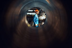 Worker with wrench on factory, view through tube