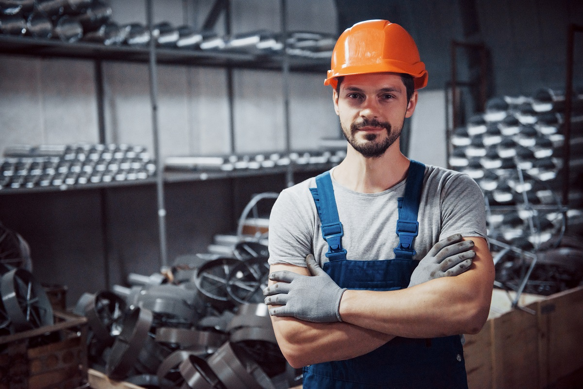 Portrait of a young worker in a hard hat at a large metalworking plant. Shiftman on the warehouse of finished products